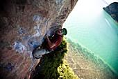 Strained male climber looks to his next move on a limestone beach cliff in Thailand Railey Beach (West), Krabi, Thailand