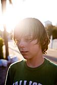A teen boy is staring with the sun shining behind him Destin, Florida, USA