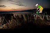 Young adult mountain biking at sunrise in Idaho Sandpoint, Idaho, USA