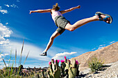 A woman jumping across a patch of cactus at the Alabama Hills above Lone Pine in California Lone Pine, California, USA