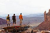 Three young men overlook a canyon after biking up the Amasa Back Trail, Moab, UT Moab, Utah, USA