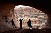 Four young men are silloutted against the mouth of a cave in Moab, UT Moab, Utah, USA