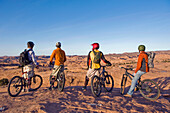 Four young men enjoy the view during a mountain bike trip on the Slickrock Trail, Moab, UT Moab, Utah, USA