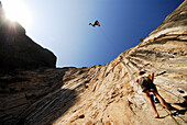 One climber pushes off into the air while rappelling above another climber El Potrero Chico, Nuevo Leon, Mexico