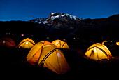 Tents illuminate the night 2, 000 ft. below the summit of Mt. Kilimanjaro Tanzania