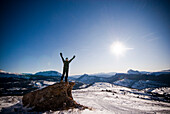 A middle aged man celebrates reaching a high point overlooking a snowy valley in the Rocky Mountains Colorado, USA