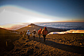 A team of hikers approach the summit of Mt. Kilimanjaro at sunrise after trekking six hours through the night Tanzania