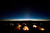 Tents illuminate the night as stars fill the sky on mMt. Kilimanjaro Tanzania