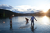 Three young adults smile while splashing water at sunset in Idaho Sandpoint, Idaho, USA