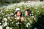 Two young women smile while reading a book in a field of wild flowers Sandpoint, Idaho, USA