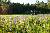 Two young women smile as they run through a field of wild flowers holding hands in Idaho Sandpoint, Idaho, USA