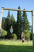 Two young women swinging smile while looking back on a summer day Sandpoint, Idaho, USA