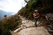 A female trekker shoulders her rucksack uphill in Nepal Annapurna Conservation Area, Nepal
