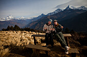 A trekking couple adjust their hats infront of the Annapurna mountain range in Nepal Annapurna Conservation Area, Nepal