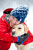 A woman gives her dog a loving hug on a snowy winter day Utah, USA