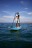 Male stand up paddling in the ocean San Diego, CA, USA