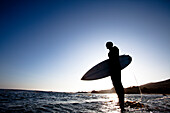 A male surfer stands on a rock while being silhouetted by the setting sun Malibu, California, United States of America