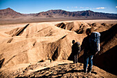 Two male hikers search to find the best route through Death Valley's Confidence Hills, in California, while on backing packing Death Valley, California, United States of America