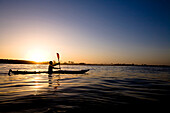 A silhouetted young man paddles a touring kayak just outside of Ventura Harbor in Ventura, California Ventura, California, United States of America