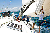 A sailor adjusts a sail with a dog on the bow during a race, La Cruz, Mexico