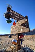 Teakettles hang on the road sign at Teakettle Junction in Death Valley National Park, California Death Valley National Park, California, USA