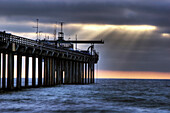 Shafts of light penetrate the clouds on a surreal afternoon at Scripps Pier in La Jolla, CA La Jolla, California, USA