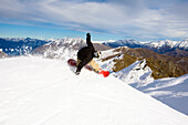 A male snowboarder blasts a heel side turn while snowboarding at Coronet Peak in Queenstown, New Zealand Queenstown, Otago, New Zealand