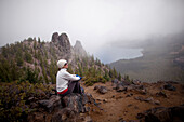 A young woman rests after hiking around the rim of Newberry Volcano east of the Cascade range near Bend, Oregon, Oregon, USA