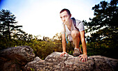 Young man climbs over a boulder while hiking up a mountain at Oak Mountain State Park in Birmingham, Alabama. (Back lit, Lens Flare), Pelham, Alabama, United States