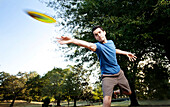 Closeup of a man making a backhanded drive playing disc golf. (Motion Blur), Birmingham, Alabama, United States