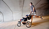 A man runs through a tunnel with his twin sons in a stroller. (Motion Blur), Helena, Alabama, United States