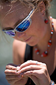 A close up of a female looking down and tying a fly to her line Jackson Hole, Wyoming, U.S.A.