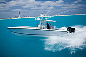 A fishing boat speeds through the blue water with the shore-line and lighthouse in the distance Florida, U.S.A.