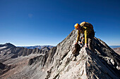 Two young men crossing an exposed ridge line with the summit behind them Aspen, Colorado, USA
