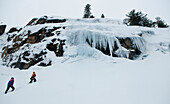 Two men hike up to the base of the ice climb in Truckee, California Truckee, California, USA