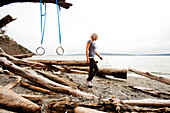 A woman performs suspension training exercises on a rustic beach Camano Island, Washington, United States