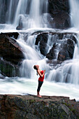 A woman performs yoga in front of a large waterfall in Lake Tahoe, California Lake Tahoe, California, USA