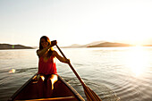 A happy young woman smiles while canoeing on a camping trip on a lake in Idaho Sandpoint, Idaho, USA