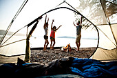 Three young adults smiling and dancing around a camp fire on a camping and kayaking trip on a lake in Idaho Sandpoint, Idaho, USA