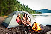 Two beautiful women laugh and smile sitting in their tent next to a campfire in Idaho Sandpoint, Idaho, USA