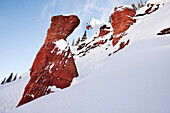A athletic skier jumping off a cliff in the backcountry on a sunny powder day in Colorado Vail, Colorado, USA