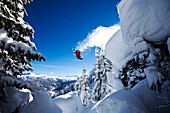 A athletic skier flipping off a cliff in the backcountry on a sunny powder day in Colorado Vail, Colorado, USA