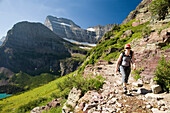 A woman in her early thirties hikes along the Grinnell Glacier trail in Glacier National Park, Montana Glacier National Park, Montana, United States of America