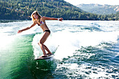 A athletic young woman smiles while wakesurfing behind a wakeboard boat on a sunny day in Idaho., Sandpoint, Idaho, USA