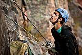 A athletic man rock climbing belays his partner in Montana., Bozeman, Montana, USA
