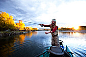 A fly fisher casting his line out of a boat while fly fishing surrounded by fall colors in Montana., Bozeman, Montana, USA