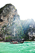 A longtail boat transporting a group of people next to huge limestone cliffs and turquoise water in Thailand., Railay, Thailand