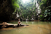 A beautiful young woman adventuring deep into a remote jungle pool relaxes in Thailand., Railay, Thailand