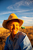 A cowgirl looks to the camera and smiles with the warm rays of the setting sun following a dusty day in the saddle., Arizona, USA