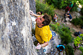 A top view on Gerome Pouvreau focusing on a difficult move while leading the climb on a limestone wall., Millau, France